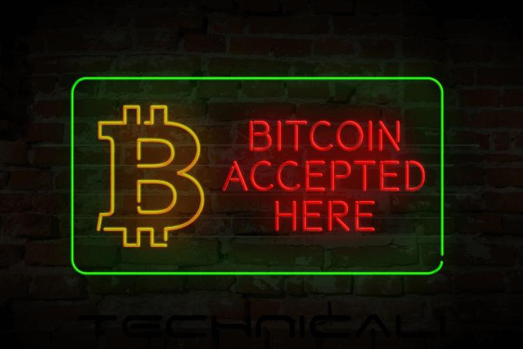 Bitcoin Accepted Here written in glow as a glow board outside merchant show
