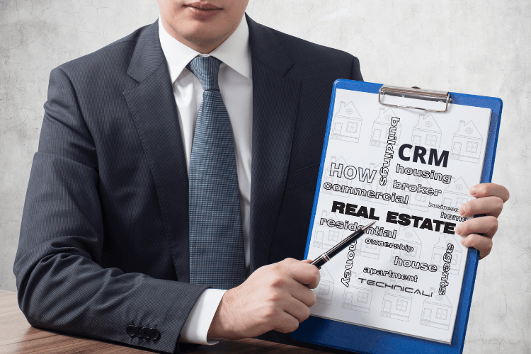 person holding board written how crm in real estate works on it.