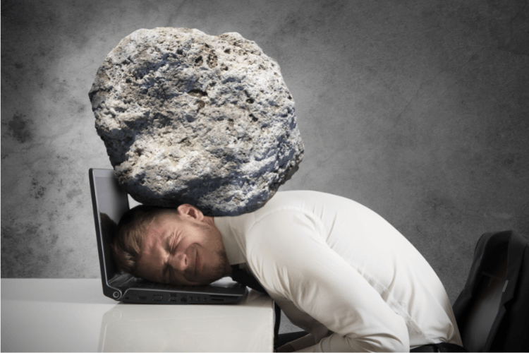 man with head on laptop and burdened by rock