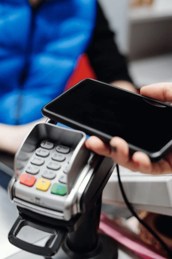 mobile in person's hand with card machine
