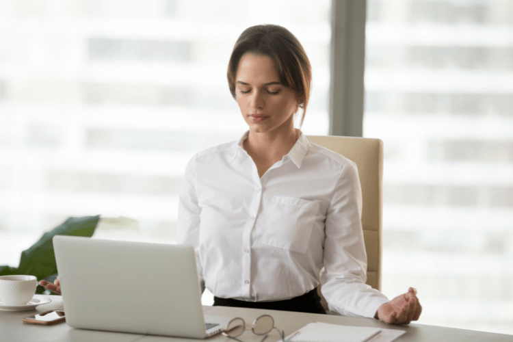 woman doing meditation on office desk in front of laptop