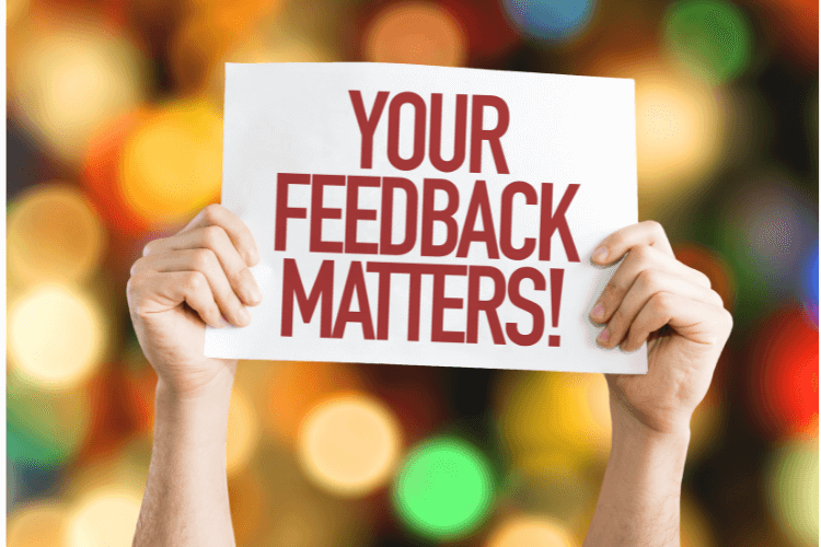 hands holding your feedback matters card with colorful lights in background