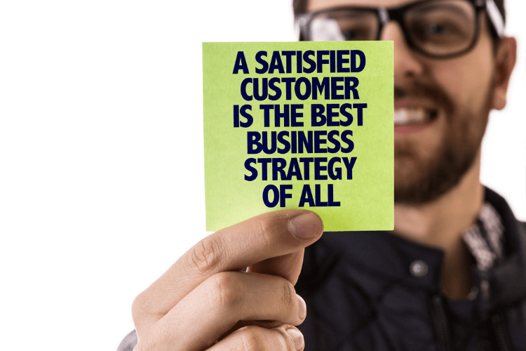 """a man holding sticky note with text """"a satisfied customer is the best business strategy of all"""